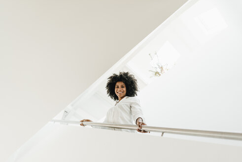 Portrait of smiling young woman in staircase - KNSF02265