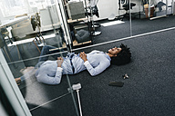 Young woman lying on the floor in office - KNSF02280