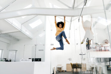 Young woman hanging on beam in office - KNSF02286