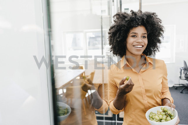 Smiling young woman holding bowl with grapes in office - KNSF02289