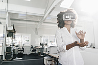 Woman wearing VR glasses in office - KNSF02307