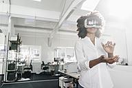 Woman wearing VR glasses in office - KNSF02307