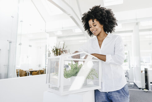 Smiling young woman in office caring for plants in glass box - KNSF02325