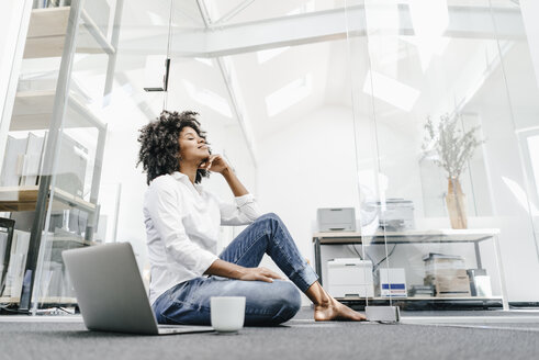 Young woman with closed eyes sitting on floor in office with laptop - KNSF02328