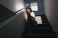 Young woman sitting on staircase in sunlight - KNSF02352