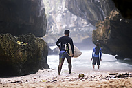 Indonesia, Bali, back view of surfer carrying surfboard - KNTF00867