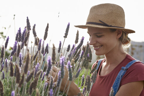 Smiling woman wearing straw hat in lavender field - PACF00060