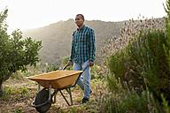 Young farmer pushing a wheelbarr - PACF00069