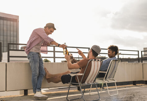 Three friends having a rooftop party - UUF11451