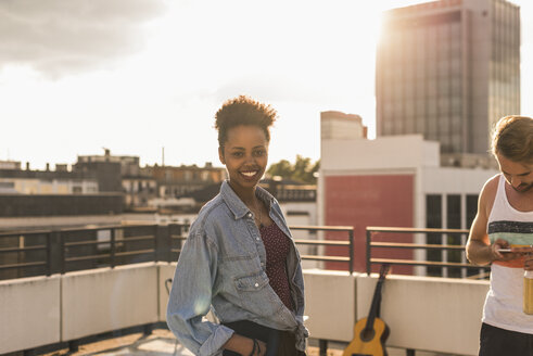 Portrait of smiling young woman on a rooftop party - UUF11478