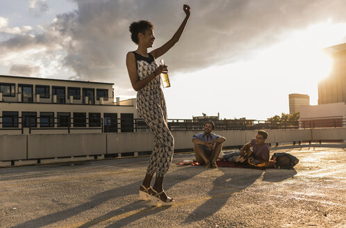 Young woman dancing on a rooftop party - UUF11481