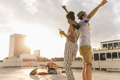 Young couple dancing on a rooftop party - UUF11484