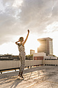 Young woman with headphones dancing on rooftop - UUF11487