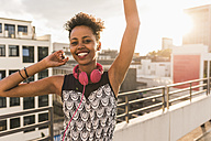 Portrait of happy young woman with headphones on rooftop - UUF11493