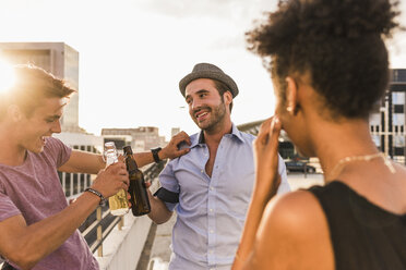 Friends clinking beer bottles on a rooftop party - UUF11502