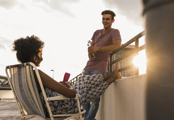 Young couple socializing on rooftop - UUF11505