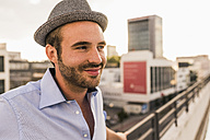 Portrait of smiling young man on rooftop - UUF11508