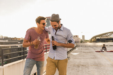 Two friends with beer bottles on rooftop - UUF11511