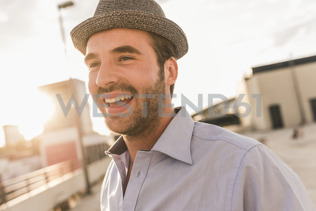 Portrait of happy young man on rooftop - UUF11514