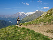 Italy Lombardy, Passo di Val Viola, Man riding e-bike in the mountains with action cam on his helmet - LAF01859