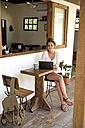 Portrait of young woman with laptop and mug of coffee sitting on veranda of a coffee shop - ECPF00047