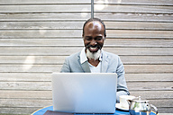 Portrait of laughing bearded man using laptop - IGGF00091