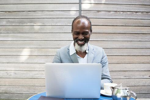 Portrait of laughing bearded man using laptop - IGGF00091