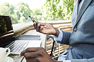 Businessman checking phone while working on his laptop on a terrace, partial view - IGGF00094