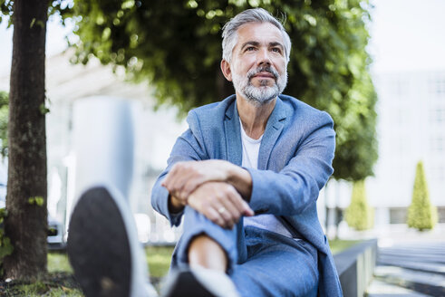 Relaxed businessman sitting outdoors on a wall - DIGF02644