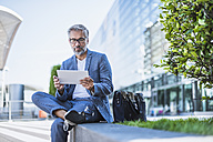 Businessman using tablet outdoors - DIGF02650