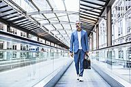 Businessman walking on moving walkway - DIGF02653