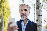 Portrait of businessman at tree checking cell phone - DIGF02656