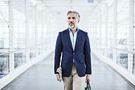 Businessman walking in passageway - DIGF02659
