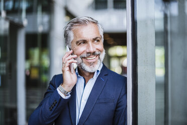 Smiling businessman on cell phone - DIGF02662