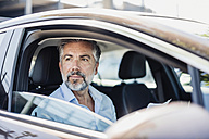 Businessman with documents in car - DIGF02668