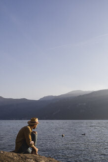Italy, Lierna, man sitting at lakeshore enjoying sunset - MRAF00220