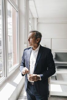 Mature businessman with glass of coffee in his office looking out of window - KNSF02358