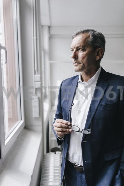 Serious mature businessman looking out of window - KNSF02361 - Kniel Synnatzschke/Westend61