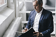Pensive businessman with notebook sitting beside window - KNSF02364