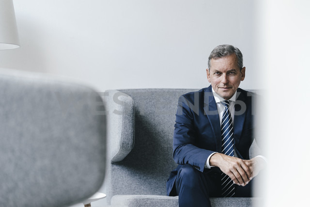 Portrait of mature businessman sitting on couch in his office - KNSF02385 - Kniel Synnatzschke/Westend61
