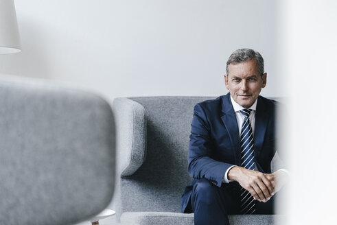 Portrait of mature businessman sitting on couch in his office - KNSF02385