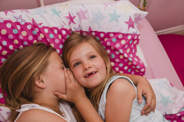 Girl lying on bed with her little sister  telling a secret - NMSF00138