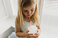 Blond little girl blowing milk bubbles - NMSF00141