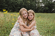 Two little sisters hugging each other on a meadow - NMSF00150