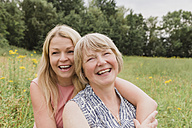 Portrait of mother and adult daughter having fun on a meadow - NMSF00153