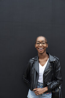 Portrait of laughing young woman wearing black leather jacket - IGGF00097