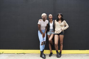 Three friends standing against black background having fun - IGGF00103
