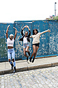 Three friends having fun jumping in the air - IGGF00106