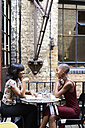 Two friends talking together in a restauarant - IGGF00115