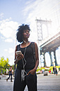 USA, New York City, Brooklyn, woman listening to music at Manhattan Bridge - GIOF03084